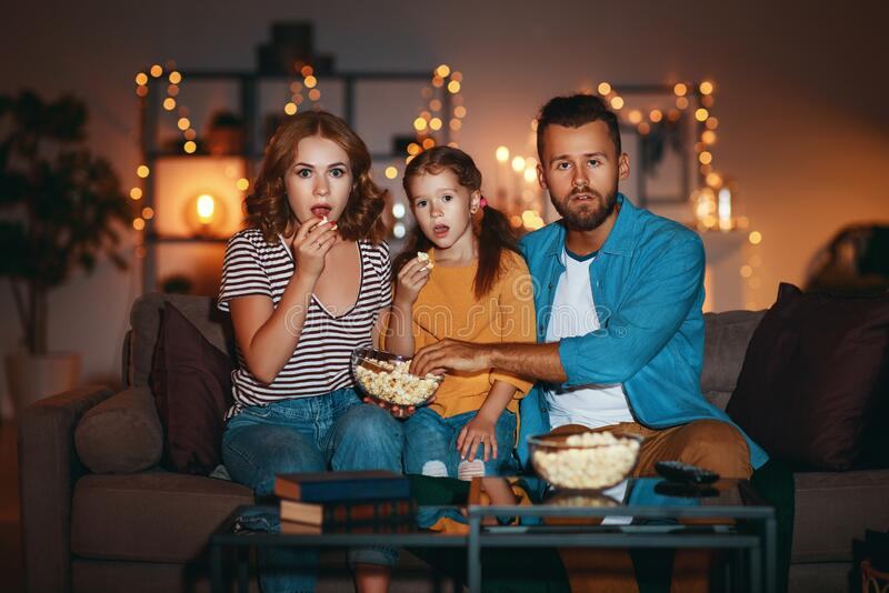 Family mother father and child daughter watching projector, TV, movies with popcorn in   evening   at home royalty free stock images