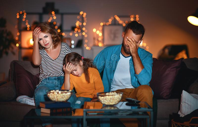 Family mother father and child daughter watching projector, TV, movies with popcorn in   evening   at home. Family mother father and child daughter watching stock photos