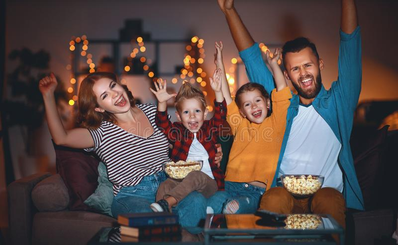 Family mother father and children watching projector, TV, movies with popcorn in   evening   at home. Family mother father and children watching projector, TV stock image