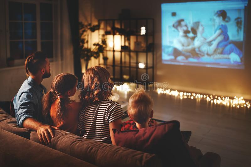 Family mother father and children watching projector, TV, movies with popcorn in   evening   at home royalty free stock images