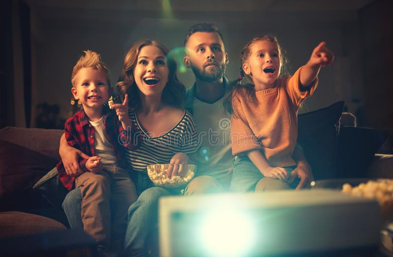 Family mother father and children watching projector, TV, movies with popcorn in   evening   at home royalty free stock image