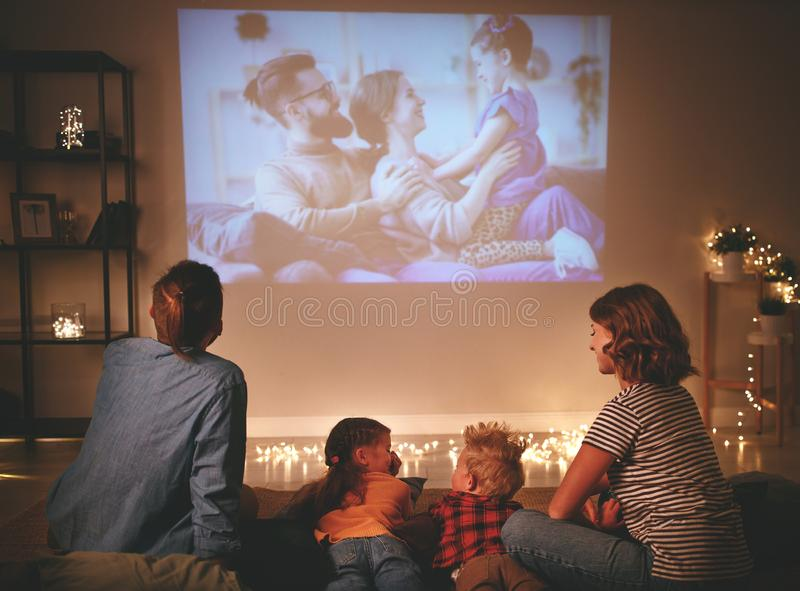 Family mother father and children watching projector, TV, movies with popcorn in   evening   at home stock images