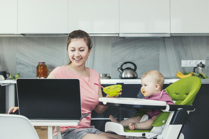 Family the mother feeds the baby in the kitchen happy together a stock photo