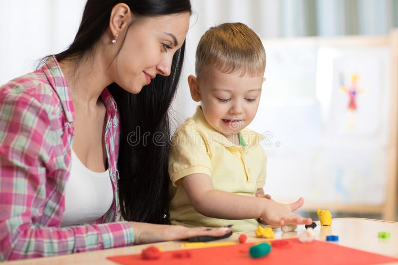 Family mother and kid boy molded from clay and play together at home. Concept of preschool or home education. royalty free stock photo