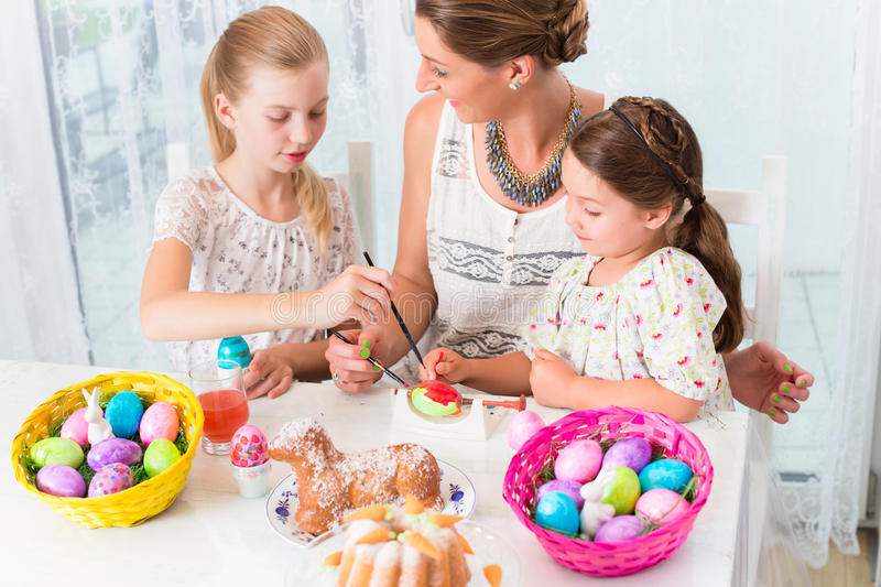 Family with mother and kids coloring Easter eggs royalty free stock photography