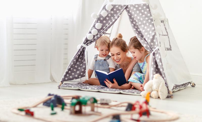 Family mother reading to children book in tent at home stock images