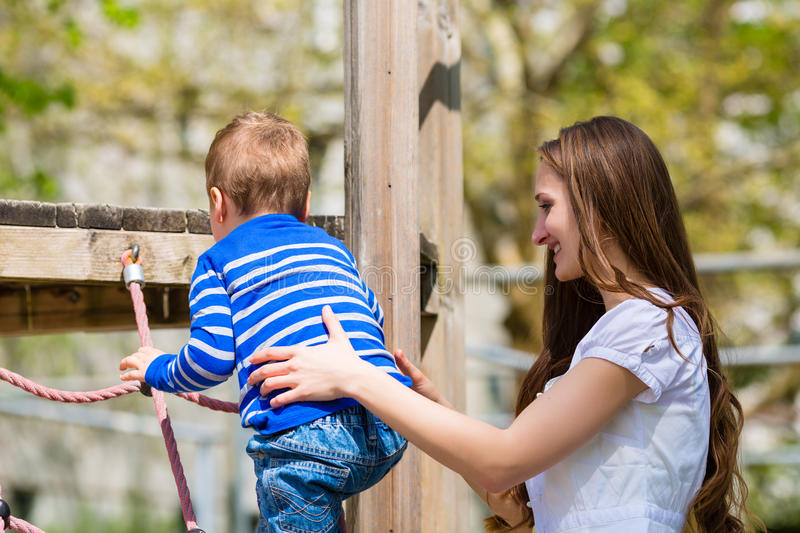 Family - Mother and son playing on a jungle gym stock photos