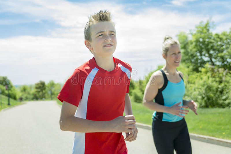 Family, mother and son are running or jogging for sport outdoors stock photo
