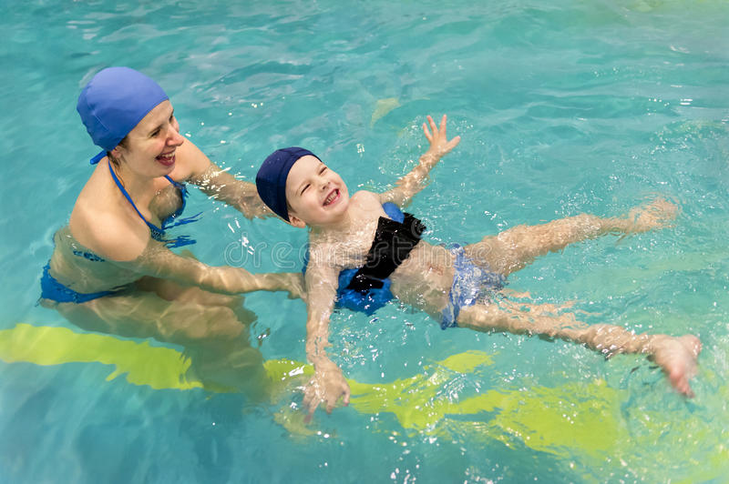 Family of mother teaching kid in swimming pool stock image
