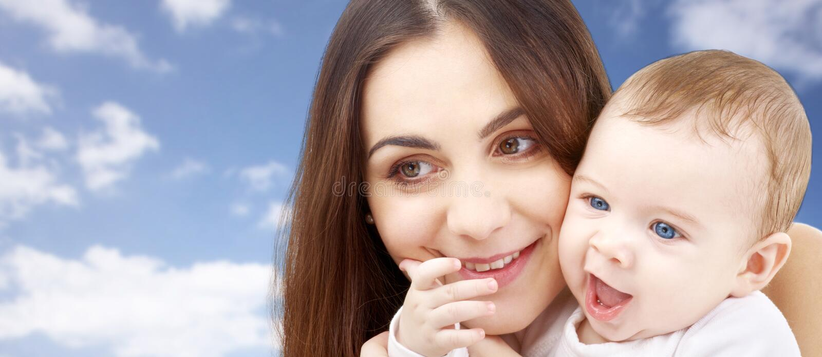 Mother with baby over sky background stock photo