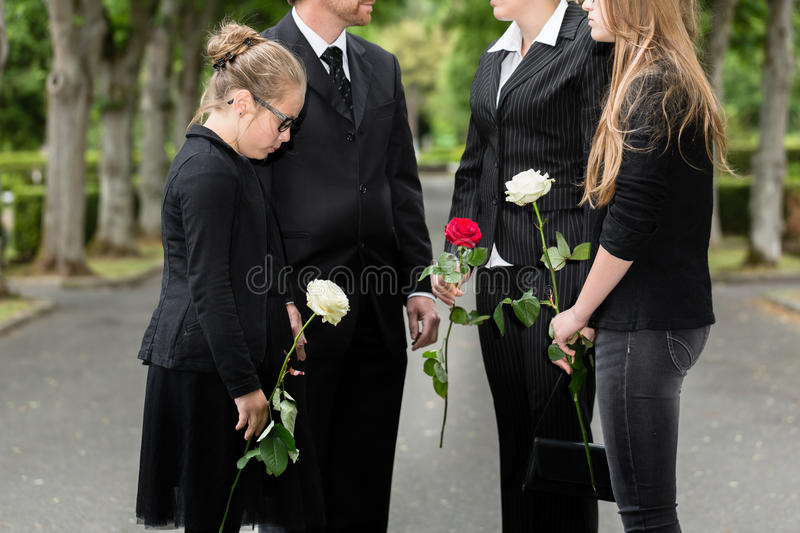 Family mourning on funeral at cemetery. Standing in group with flowers stock image