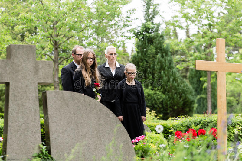 Family mourning at grave on cemetery royalty free stock photography