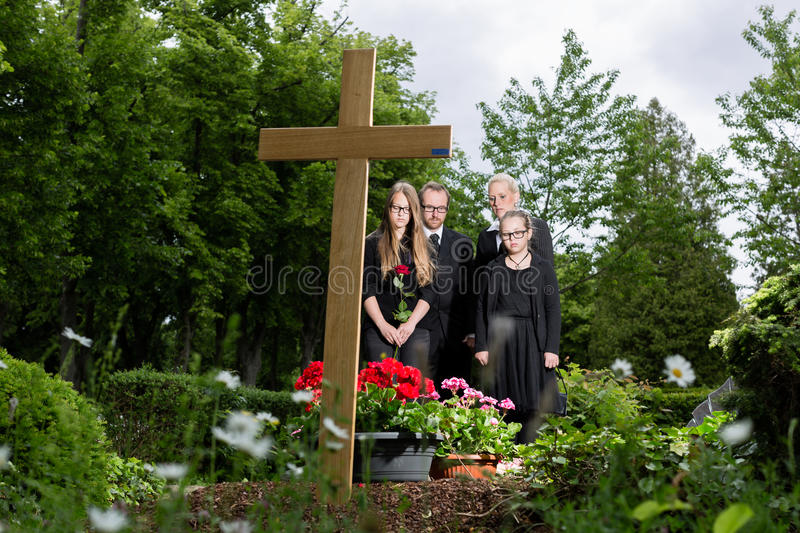 Family mourning at grave on cemetery. Family mourning at grave on graveyard or cemetery royalty free stock image
