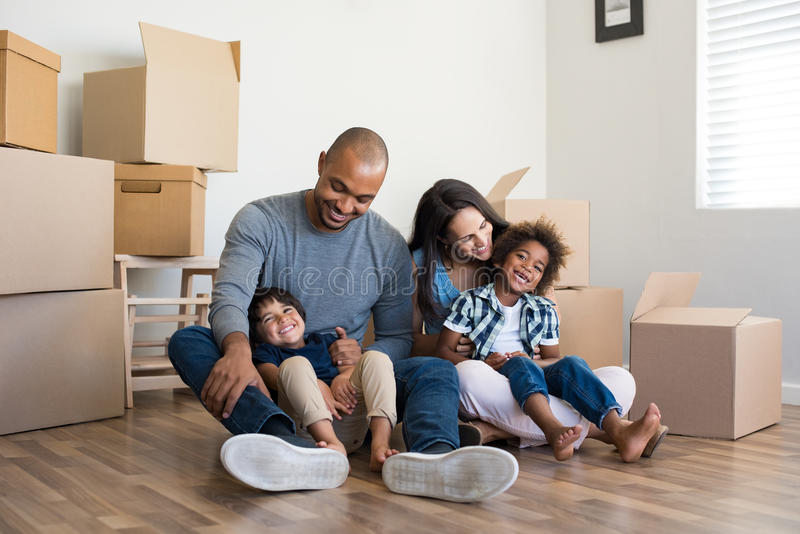 Family moving home. Happy family with two children having fun at new home. Young multiethnic parents with two sons in their new house with cardboard boxes royalty free stock photos