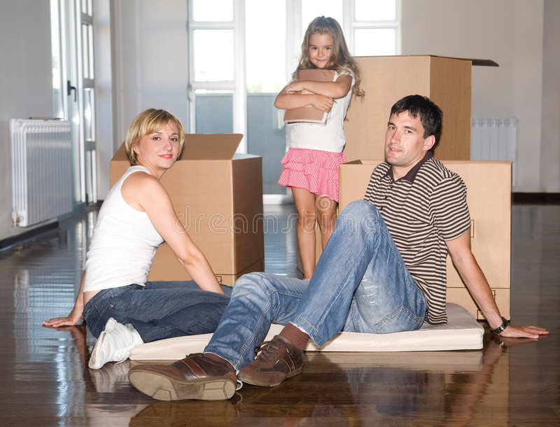 Family moving house. Young family moving house, little girl packing her things in the box stock photography