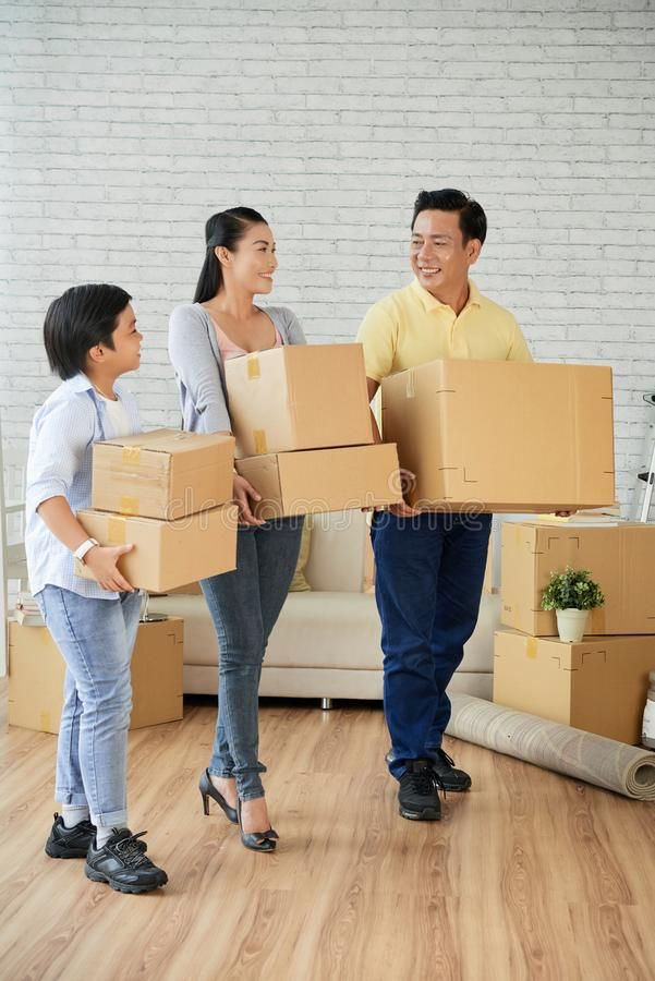 Family moving in new house. Cheerful Asian family with stack of boxes standing in their new apartment stock photo