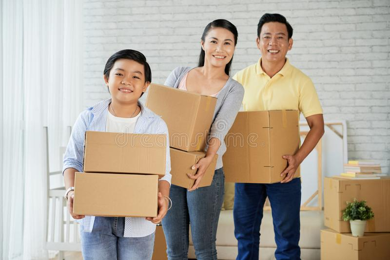 Family moving to new home. Happy smiling Asian family with many boxes standing in their new house royalty free stock photos