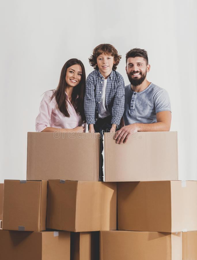 Family Moving to New Place and Stands with Boxes. Family Moving to New Place and Stands with Cardboard Boxes. Moving to New House Concept. Relocation to New stock photography