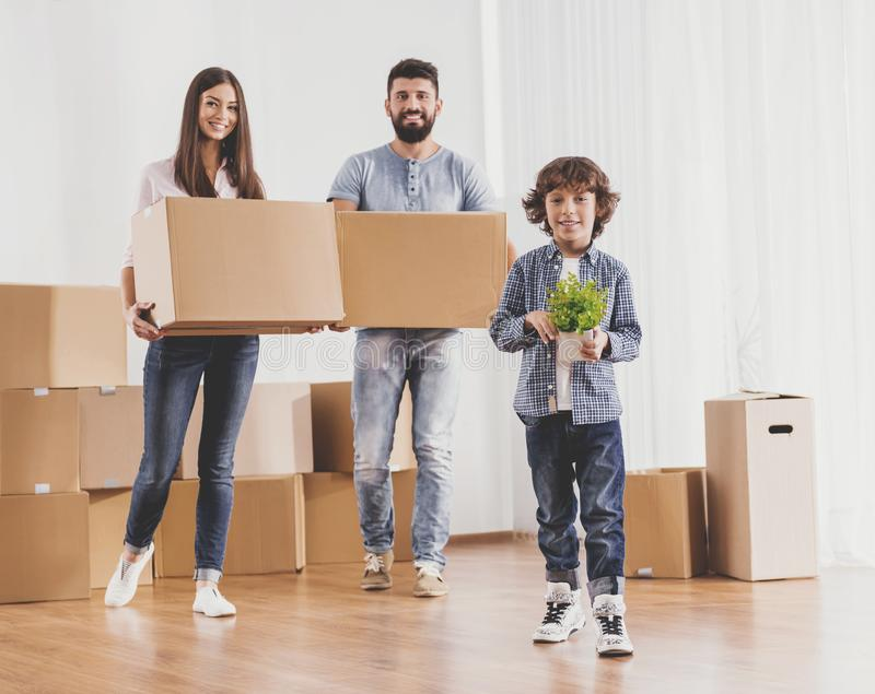 Family Moving to New Place and Stands with Boxes. Family Moving to New Place and Stands with Cardboard Boxes. Moving to New House Concept. Relocation to New royalty free stock images