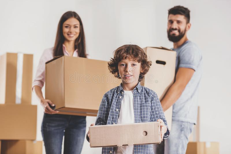 Family Moving to New Place and Stands with Boxes. Family Moving to New Place and Stands with Cardboard Boxes. Moving to New House Concept. Relocation to New royalty free stock photography