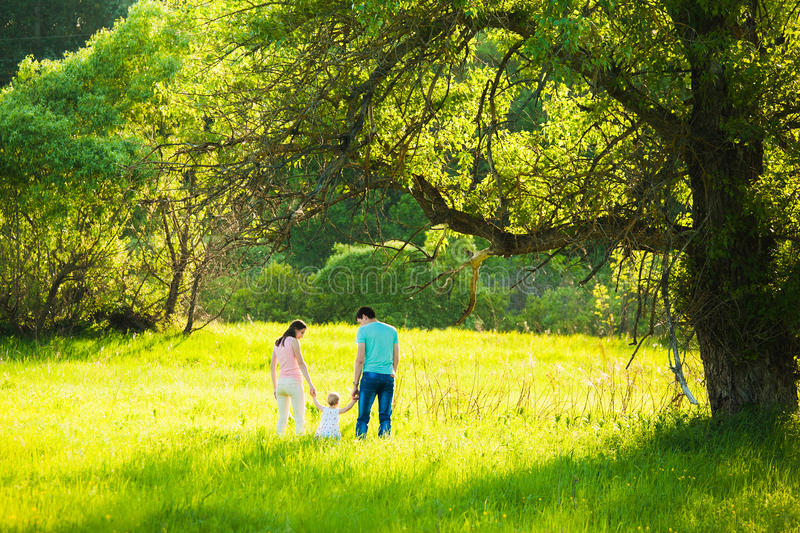 Family of mum, dad and little daughter walking together in beaut royalty free stock image