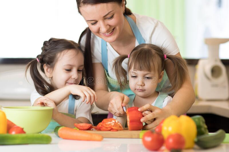 Family mum with daughters chopping vegetables in home kitchen stock image