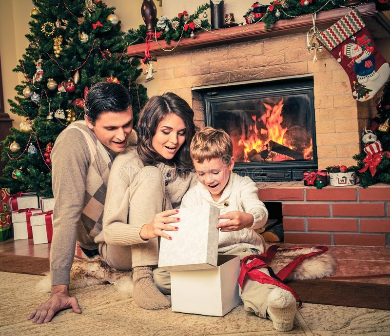 Family near fireplace in Christmas decorated house. Interior with gift box royalty free stock photography