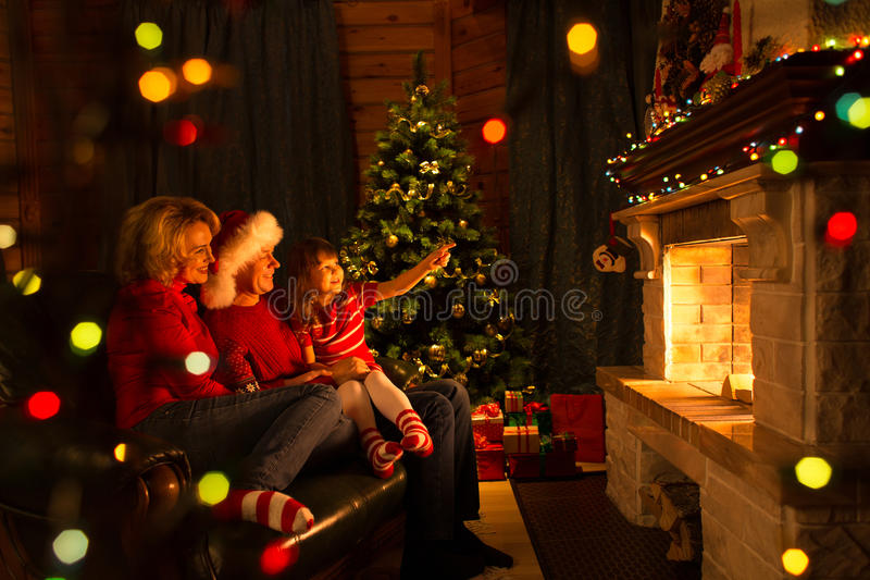 Family near fireplace and Christmas tree in festive decorated house interior. Family near fireplace and Christmas tree in festival decorated house interior royalty free stock image