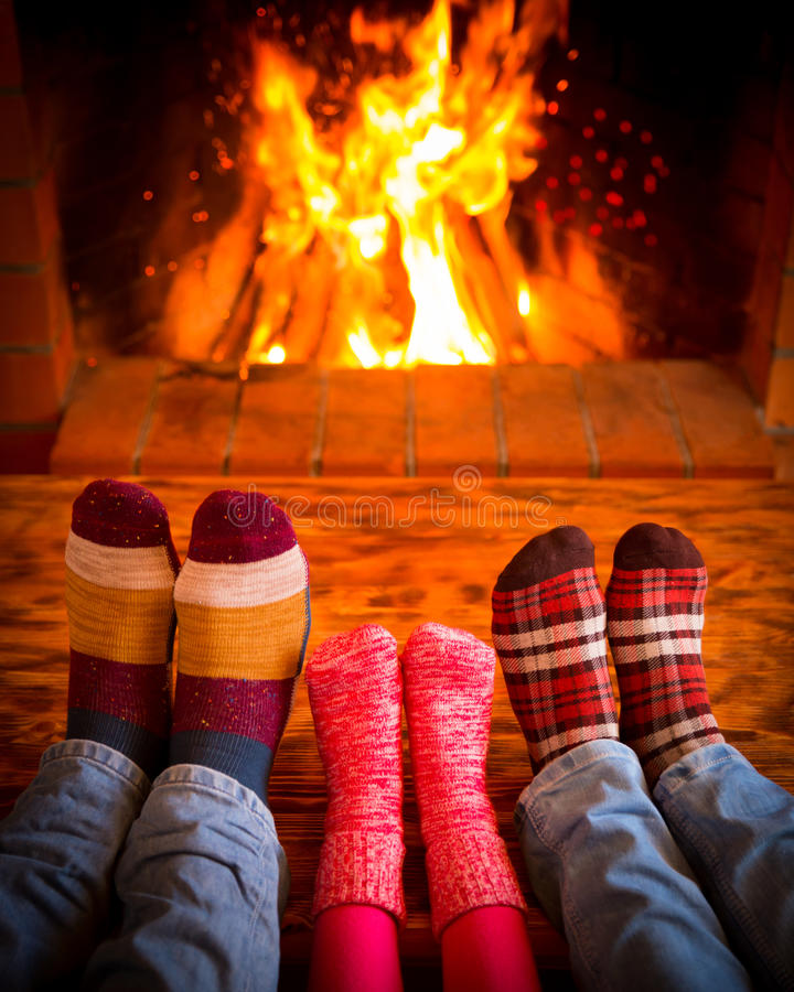 Family near fireplace. Family relaxing at home. Feet in Christmas socks near fireplace. Winter holiday concept royalty free stock photography