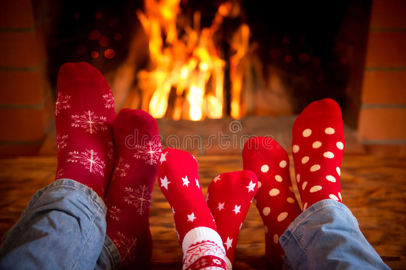 Family near fireplace. Family relaxing at home. Feet in Christmas socks near fireplace. Winter holiday concept