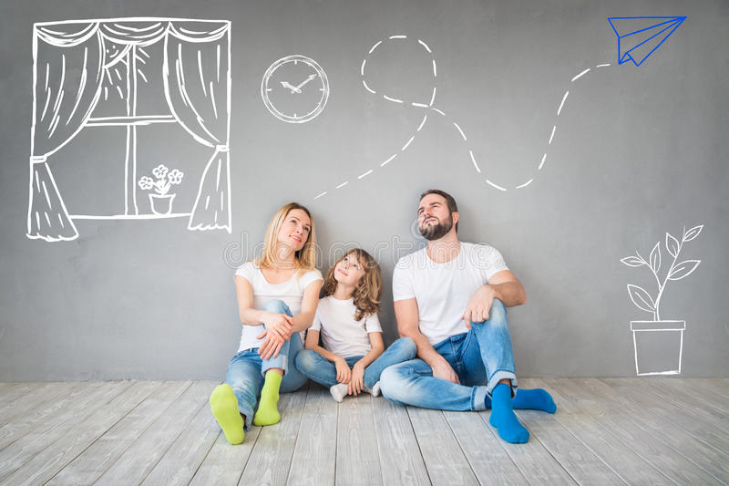 Family New Home Moving Day House Concept. Happy family sitting on wooden floor. Father, mother and child having fun together. Moving house day, new home and
