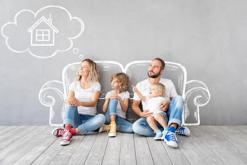 Family New Home Moving Day House Concept. Happy family with two kids playing into new home. Father, mother and children having fun together. Moving house day and royalty free stock photos