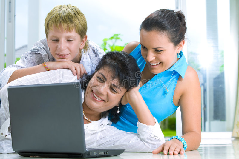 Family with notebook. Portrait of happy family getting busy with laptop stock image