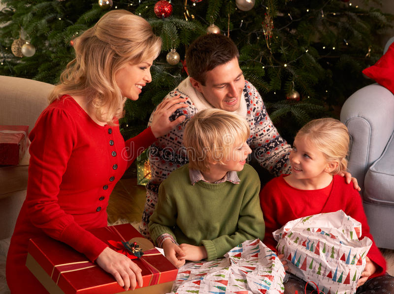Family Opening Christmas Gifts At Home. Smiling stock photography