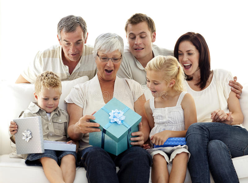 Family opening presents in grandmother's birthday. Family at home opening presents in grandmother's birthday royalty free stock photo