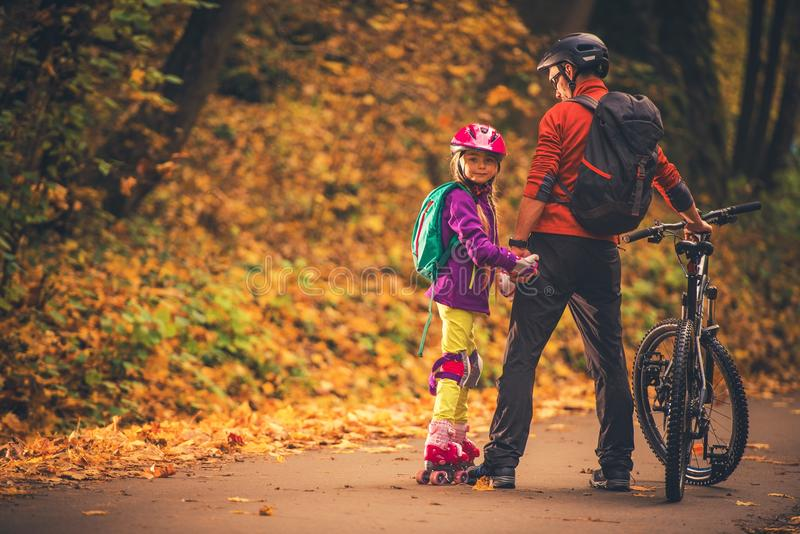 Family Outdoor Activities. Father and Daughter in the Park. Biking and Roller Skates royalty free stock image