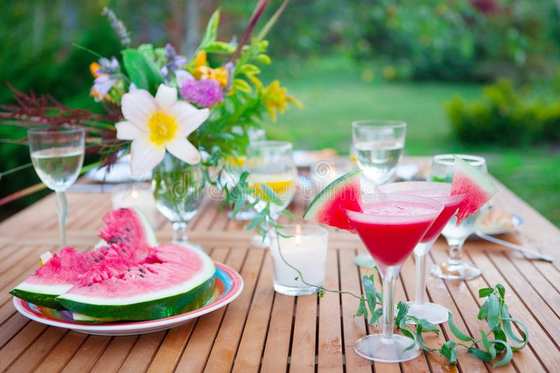 Family outdoor dinner in the garden in summer at sunset. Picnic. Two glasses of watermelon cocktail. Family outdoor dinner in garden in summertime at sunset stock photography