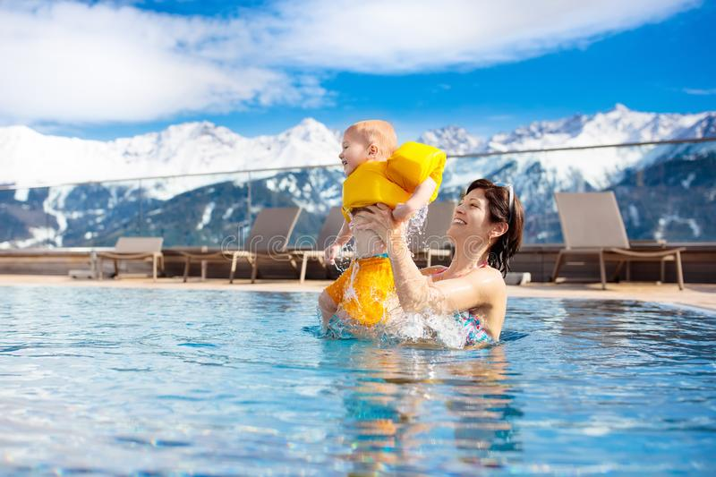 Family in outdoor swimming pool of alpine spa resort. Mother and baby play in outdoor swimming pool of luxury spa alpine resort in Alps mountains, Austria royalty free stock image