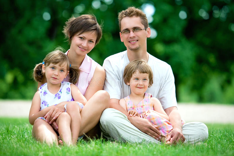 Family outdoors. Young Family Sitting on the Grass in Park