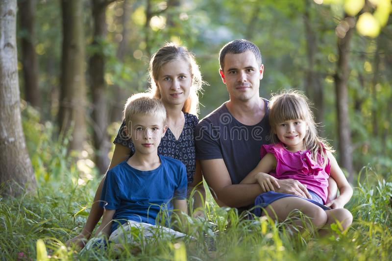 Family outdoors in forest. Portrait of young father, mother, daughter and son outsine in green woods stock images