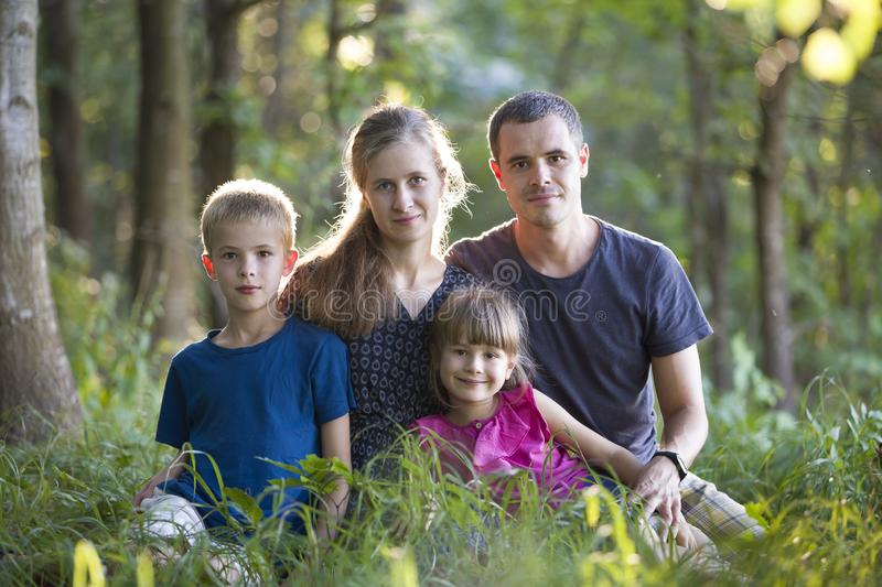 Family outdoors in forest. Portrait of young father, mother, daughter and son outsine in green woods royalty free stock images