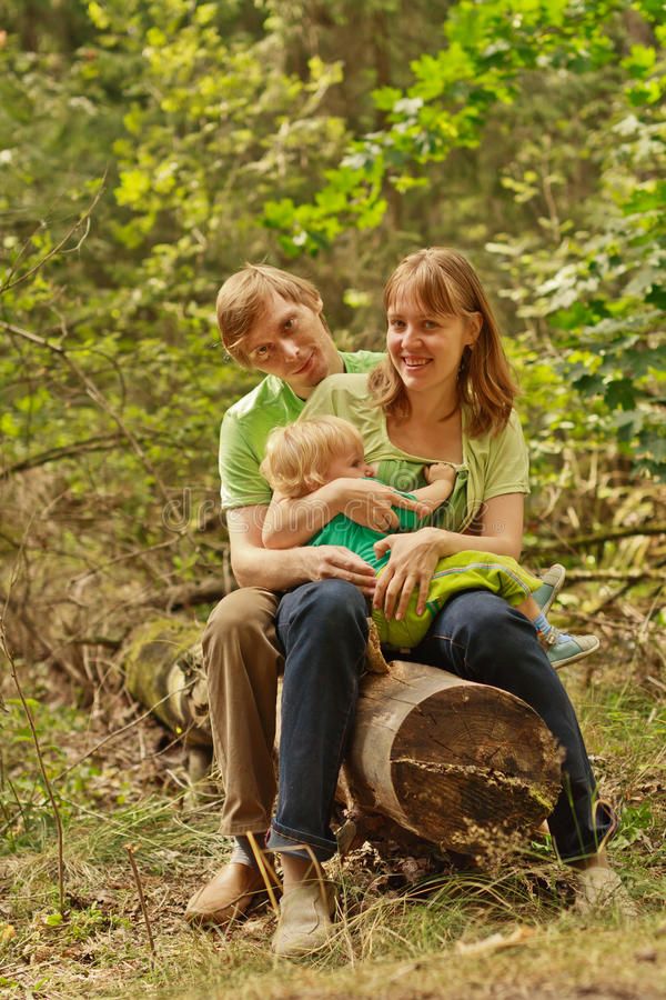 Family outdoors sitting on log smiling royalty free stock photography