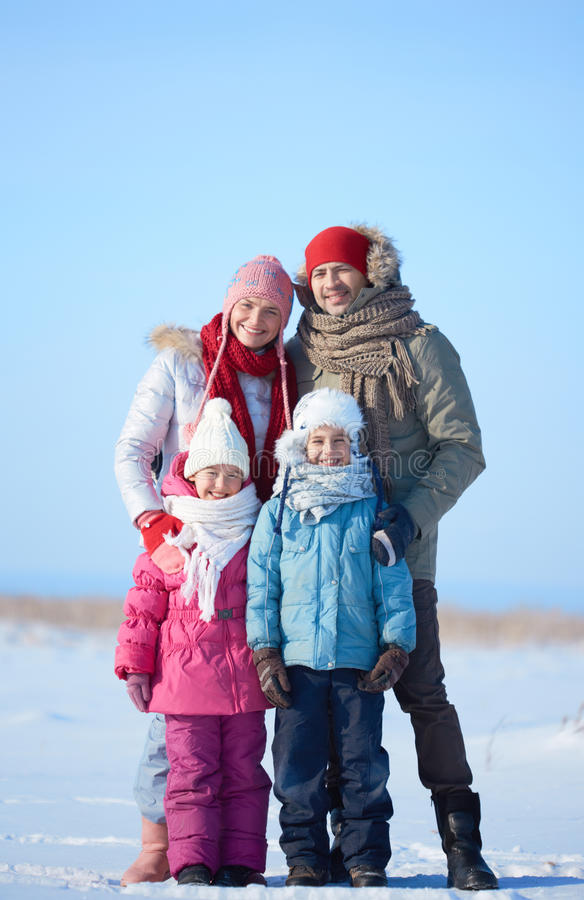 Family outside. Happy parents and their kids in winterwear looking at camera outside royalty free stock image