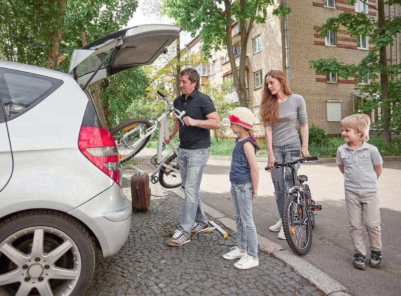Family is packing their bikes into the trunk of a car royalty free stock photo