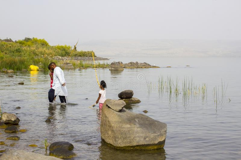 A family paddling in the water at the western shore of the Sea of Galilee royalty free stock photo