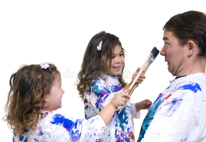 Family painting. A father and his two daughters having fun painting royalty free stock image