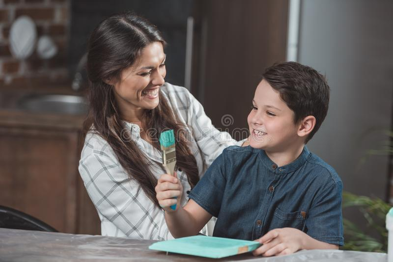 Little son and his beautiful mother laughing while painting a part of crafting royalty free stock images