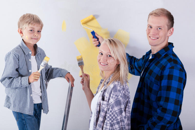 Family painting wall in new house royalty free stock photo