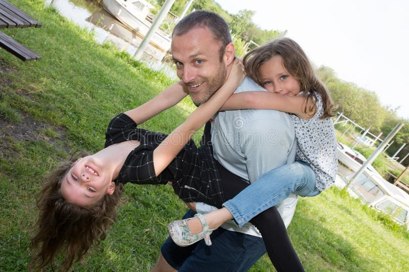 Family parenthood fatherhood concept happy man father and two little girl daughter in piggyback having fun in summer. Family parenthood fatherhood concept happy stock image