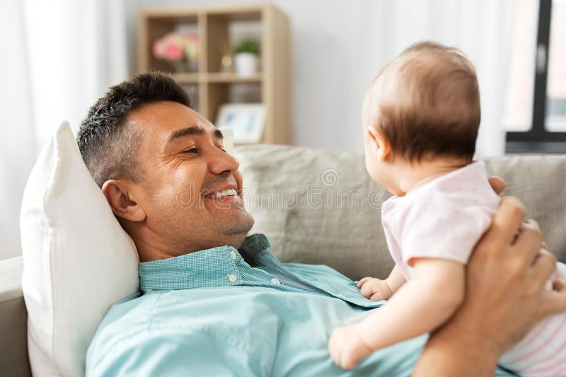 Middle aged father with baby lying on sofa at home royalty free stock photos